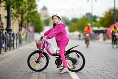 Cute little girl riding a bike in a city wearing helmet on summer day Stock Photos