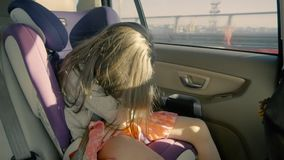 Cute little girl riding in the car at back seat and sleeping. Adorable girl