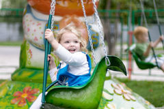 Cute little girl riding on a carousel Stock Images