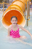 Cute little girl riding down a water slide at a water park Stock Photography