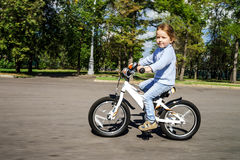 Cute little girl riding fast by bicycle Royalty Free Stock Photo