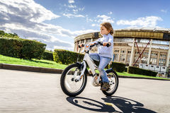 Cute little girl riding fast by bicycle Royalty Free Stock Image