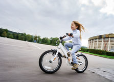 Cute little girl riding fast by bicycle. In public park stock images