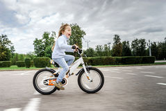 Cute little girl riding fast by bicycle Royalty Free Stock Photos