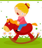 A cute little girl is riding on her rocking horse Stock Photos