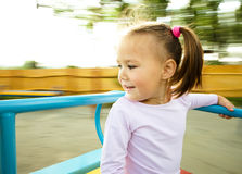 Cute little girl is riding on merry-go-round Stock Photo