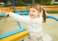 Cute little girl is riding merry-go-round Stock Photography