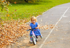 Cute little girl riding runbike in autumn Royalty Free Stock Images