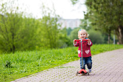 Cute little girl riding scooter in park Royalty Free Stock Photo