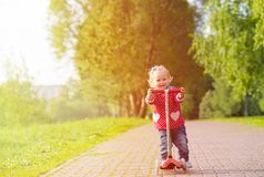 Cute little girl riding scooter in summer park Stock Photography