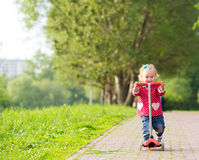 Cute little girl riding scooter in summer park Stock Images