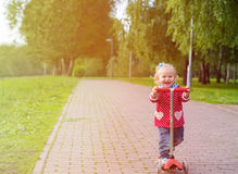 Cute little girl riding scooter in summer park Royalty Free Stock Photo