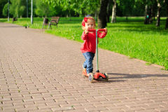 Cute little girl riding scooter in summer park Royalty Free Stock Images