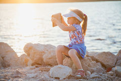 Cute little girl on rocky beach with digital tablet Stock Photography