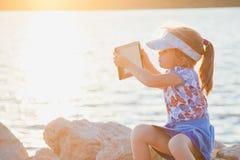 Cute little girl on rocky beach with digital tablet Stock Photo