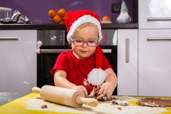 Girl with roller pin preparing Christmas cookies Royalty Free Stock Image