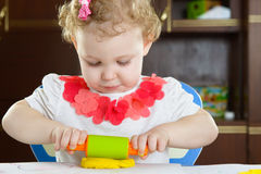 Cute little girl rolling clay dough with Stock Photos