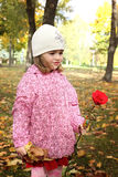 Cute little girl with rose in autmn park Royalty Free Stock Image
