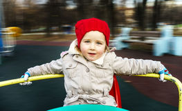 Cute little girl rounding on merry-go-round Royalty Free Stock Photography