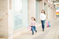 Mother and daughter having fun while shopping in mall. Cute little girl running away from her mother outside a shopping mall after shopping Royalty Free Stock Photography