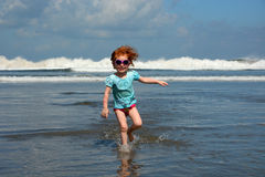 Cute little girl running away from ocean waves at the Bali beach Royalty Free Stock Photo
