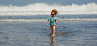 Happy Cute little girl running away from ocean waves at the Bali beach Royalty Free Stock Image