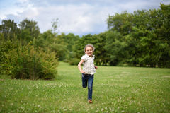 A cute little girl running barefoot on the bright green grass Royalty Free Stock Image