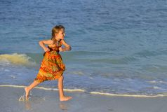 Cute little girl running on sandy beach in sunset. Cute little girl running on the beach in sunset light. Cuba. Caya Coco Stock Images