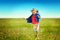 Cute little girl running on meadow in a field. Stock Photo