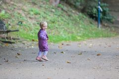 Cute little girl running in the park. Two years old girl with beautiful blue eyes is walking in the park Stock Photo