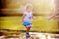 Cute little girl running through puddles. In the garden and adult hands catching her Stock Images