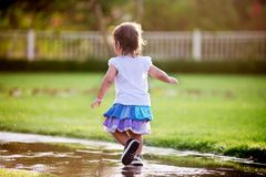 Cute little girl running through puddles. In the garden wearing wet dress Royalty Free Stock Photography