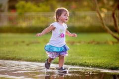 Cute little girl runnung through puddles. Cute little girl running through puddles and splashing the water in the garden wearing wet dress and smiling Royalty Free Stock Image