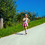 Cute little girl running on the road, energy concept Stock Photos