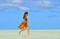 Cute little girl running on sandy beach in sunset. Cute little girl running on the beach in sunset light. Cuba. Caya Coco Royalty Free Stock Images