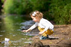 Cute little girl runs a paper boat in the stream Stock Photos