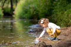 Cute little girl runs a paper boat in the stream Stock Image