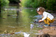 Cute little girl runs a paper boat in the stream Royalty Free Stock Image