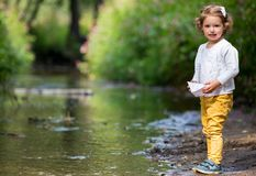 Cute little girl runs a paper boat in the stream Royalty Free Stock Photos