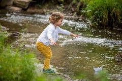 Cute little girl runs a paper boat in the stream Stock Photo