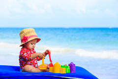 Cute little girl with sand toys on the beach Stock Images