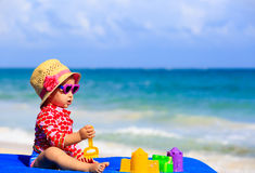 Cute little girl with sand toys on the beach Stock Photo