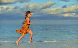 Cute little girl on sandy beach in sunset light. Blue ocean background. Cuba. Caya Coco Royalty Free Stock Photo