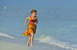 Cute little girl on sandy beach in sunset light. Blue ocean background. Cuba. Caya Coco Stock Photography
