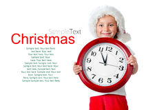 Cute little girl in santa cap with a clock Royalty Free Stock Photo