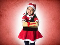 Cute Little Girl in Santa Claus costume holding a Christmas Box Stock Photo