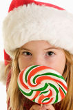 A Cute Little Girl in A Santa Claus Hat and Big Christmas Lollipop. A cute little girl with a red Santa hat and a big swirled lollipop on a white background Stock Images
