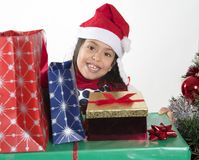 Cute Little Girl in Santa Claus hat holding Christmas Presents Royalty Free Stock Photography