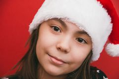 Cute little girl in Santa Claus hat on red background. royalty free stock photography