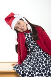 Cute Little Girl in Santa Claus hat sitting and Smiling at Xmas Royalty Free Stock Images